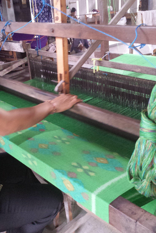 Tissage de l'Endek. On voit clairement les fils de trame pré-teints qui viennent former les motifs sur le tissu lors du tissage.